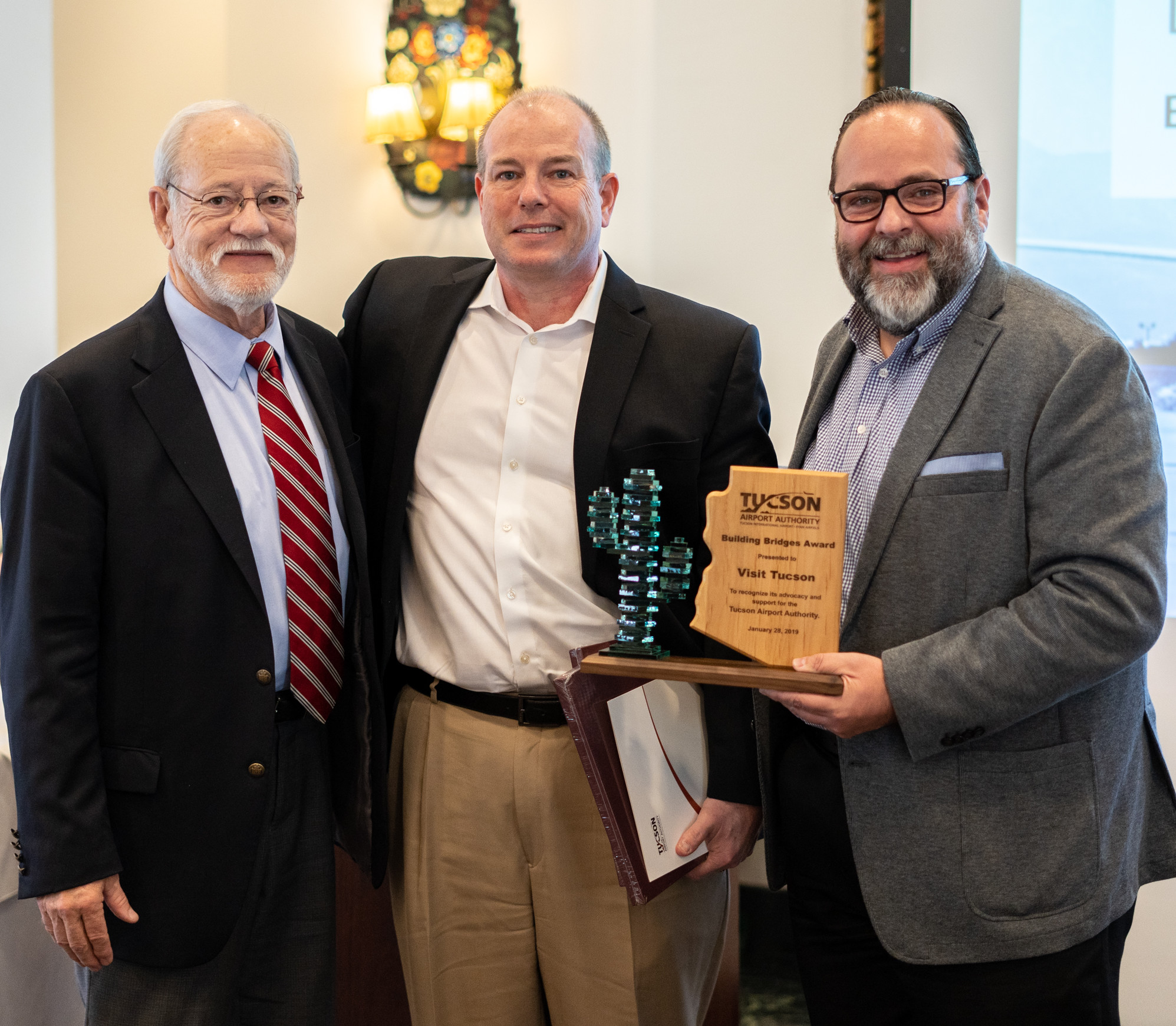 TAA Board Secretary Bruce Dusenberry, left, with Visit Tucson President and CEO Brent DeRaad and Executive Vice President Felipe Garcia receiving the Building Bridges Award.